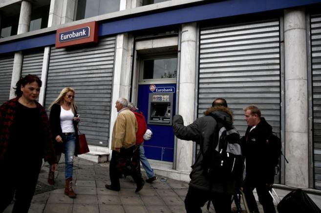 Varias personas pasan por delante del nacionalizado banco griego...