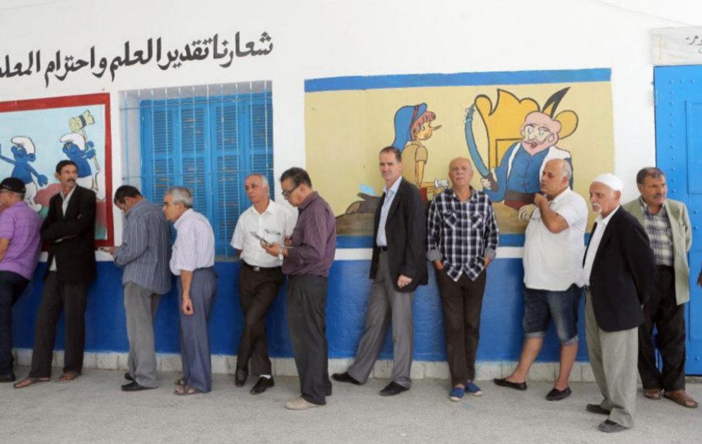 Una fila de hombres que esperan su turno para emitir su voto en las...
