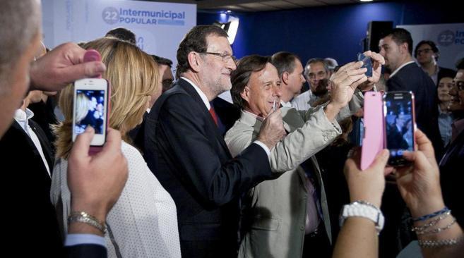 Militantes del PP, ayer en Murcia, esperan para hacerse un 'selfie'...