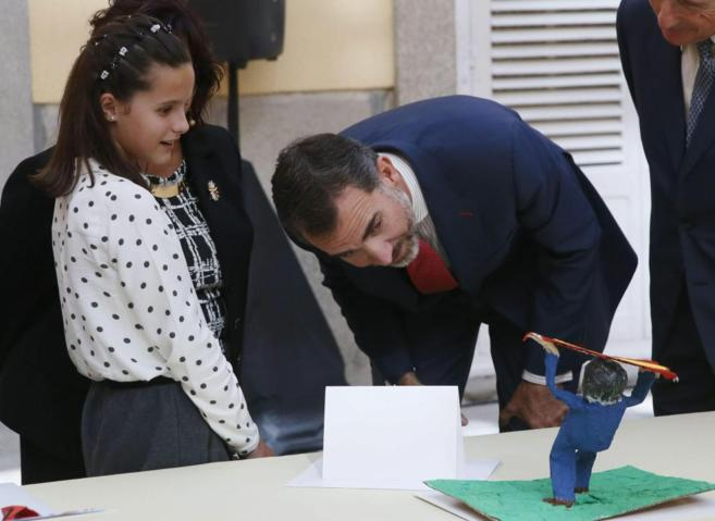 El Rey observa el trabajo de una de las niñas ganadoras.