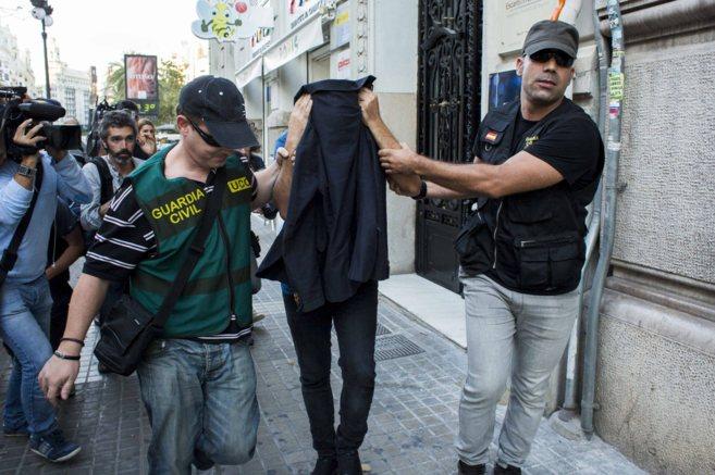 Agentes de la Guardia Civil con uno de los detenidos tras proceder al...