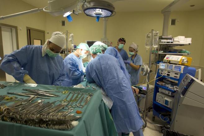 Varios profesionales sanitarios trabajando en equipo en un quirófano.