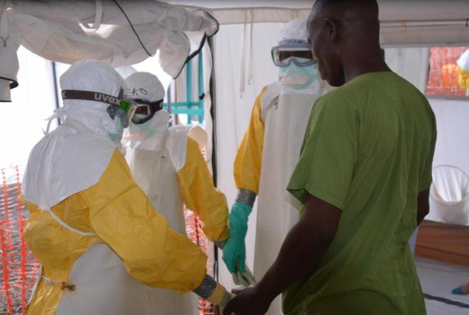 Trabajadores de salud se prueban el equipo de protección individual...