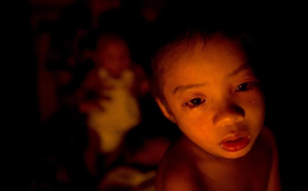 Un niño que duerme en la calle con su familia, en Manila.