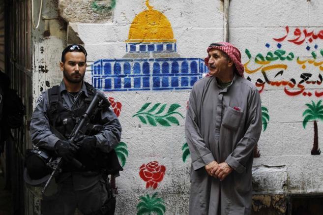 Un policía israelí, junto a un palestino en la ciudad vieja de...