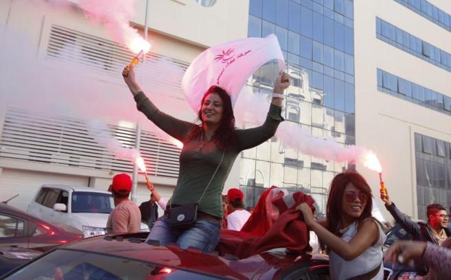 Simpatizantes del partido laico vencedor lo celebran en las calles de...