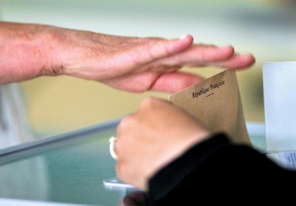Una ciudadana francesa introduce su papeleta en una urna en unas...