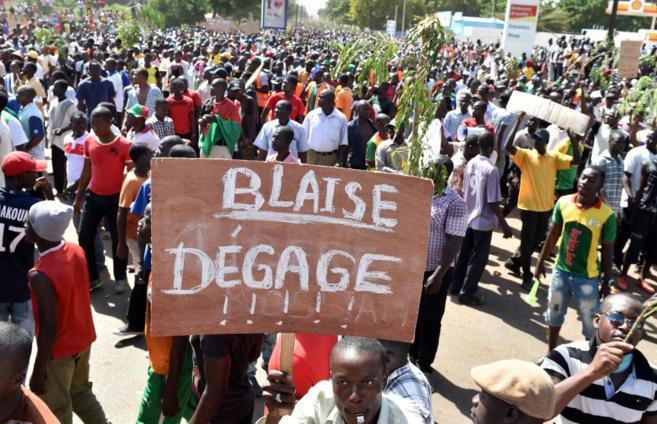 """Un manifestante muestra un cartel donde se lee """"Blaise vete""""..."""