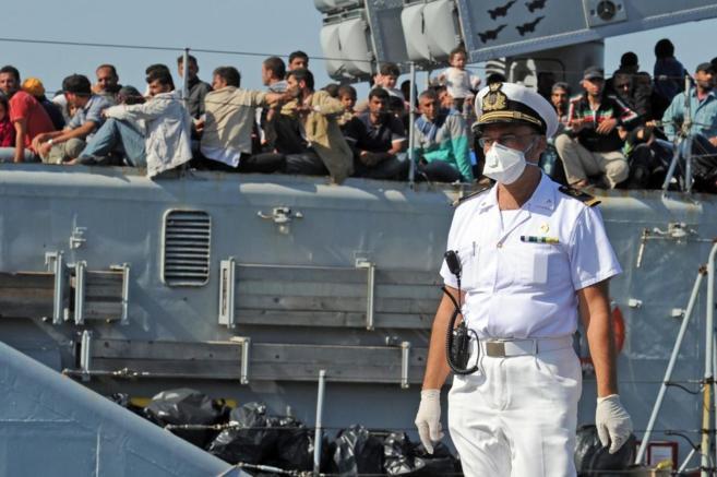 Un miembro de la Armada italiana, ante un barco lleno de inmigrantes...