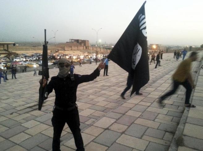 Un combatiente del IS ondea una bandera del Estado Islámico y el...