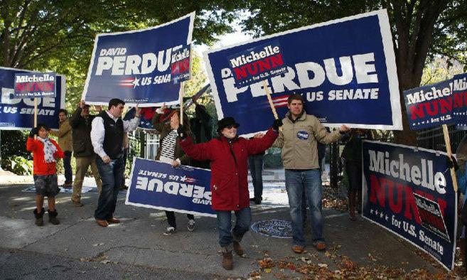 Simpatizantes de los candidatos al Senado David Perdue y Michelle...
