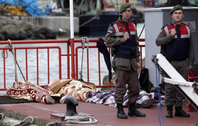 Dos agentes turcos custodian los cadáveres de los inmigrantes...