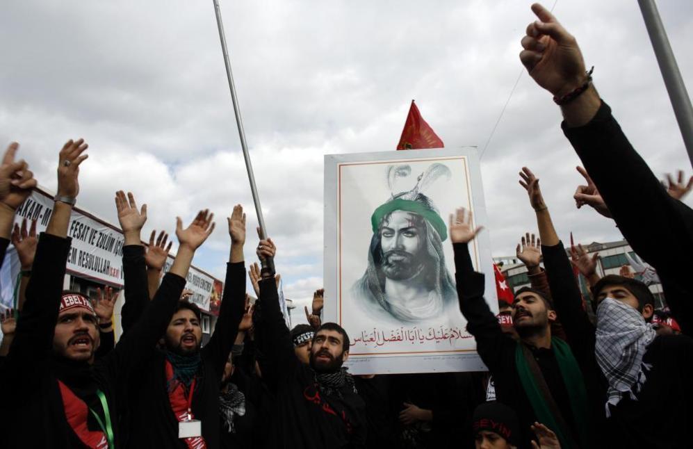 Un grupo de hombres grita consignas islámicas y exhibe un retrato del...