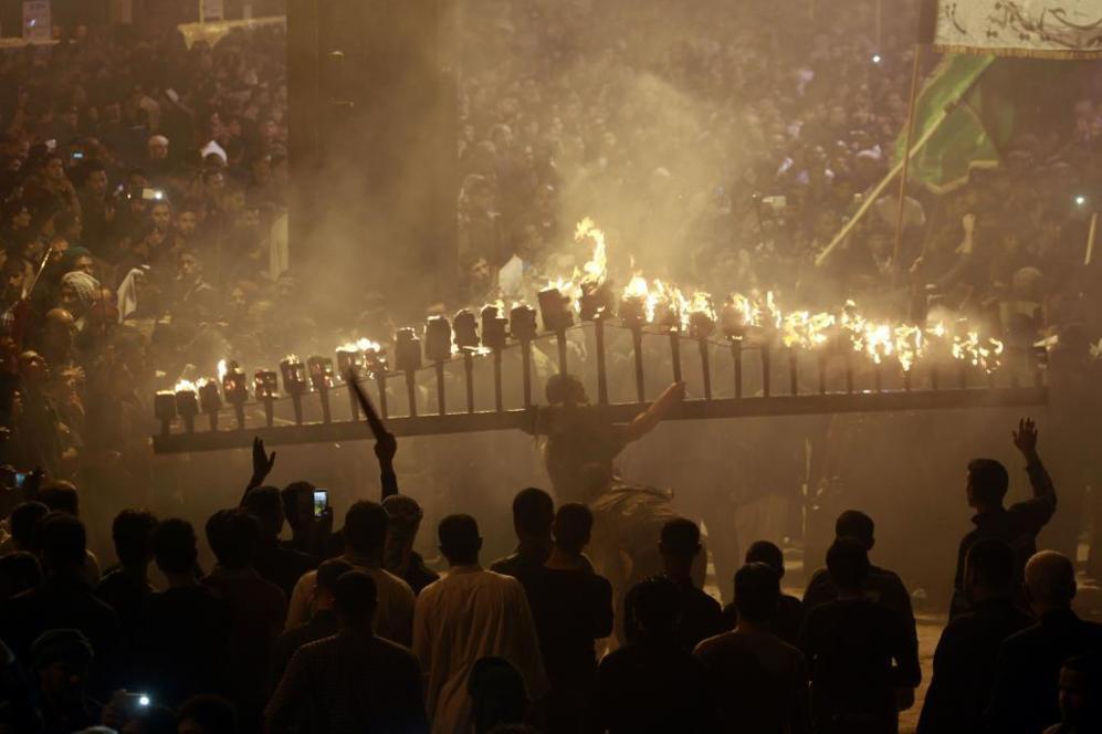 Peregrinos rezan durante una ceremonia con fuego en la ciudad iraquí...