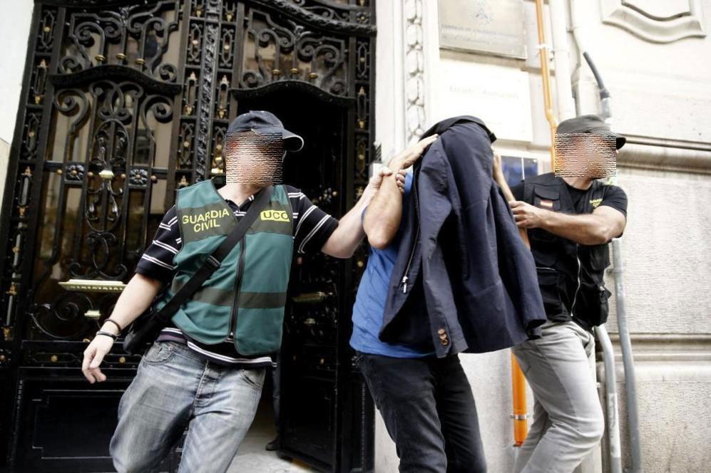 Dos agentes escoltan a un detenido durante el registro de la sede en...