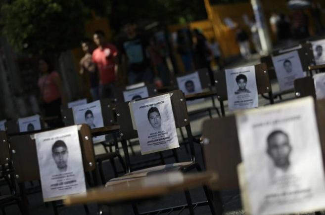 Las fotografías de los estudiantes desaparecidos se colocan sobre sus...