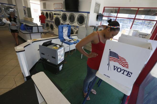 Una joven acude a votar en una cabina instalada dentro de una...