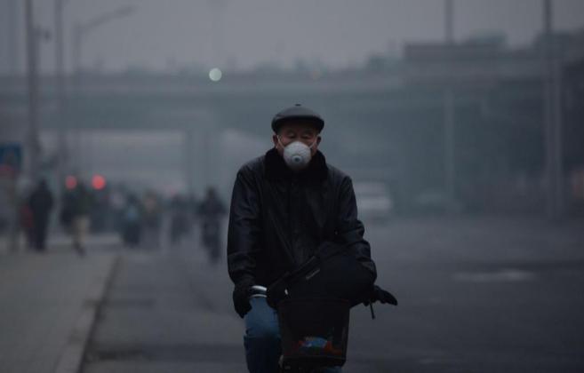 Un hombre se protege con una máscara mientras circula en bicicleta...