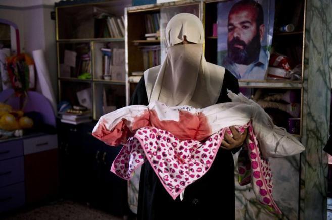 Una madre palestina sostiene el cadáver de su hija de año y medio...