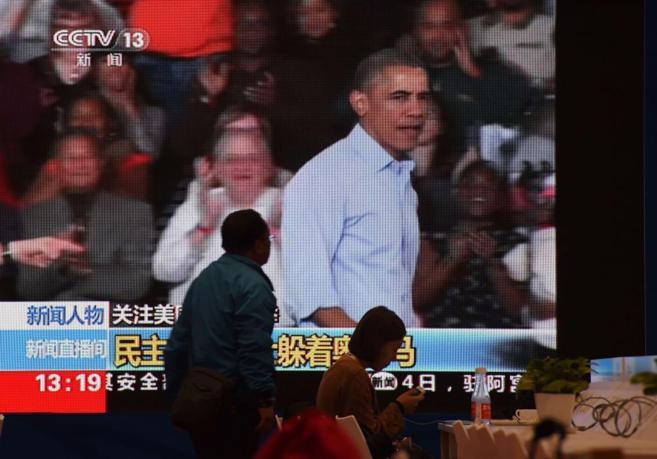 Un reportero pasa frente a una pantalla de televisión con la imagen...