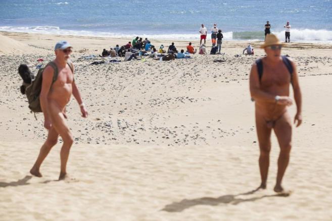 Dos turistas pasan cerca de los inmigrantes en la playa de Maspalomas.