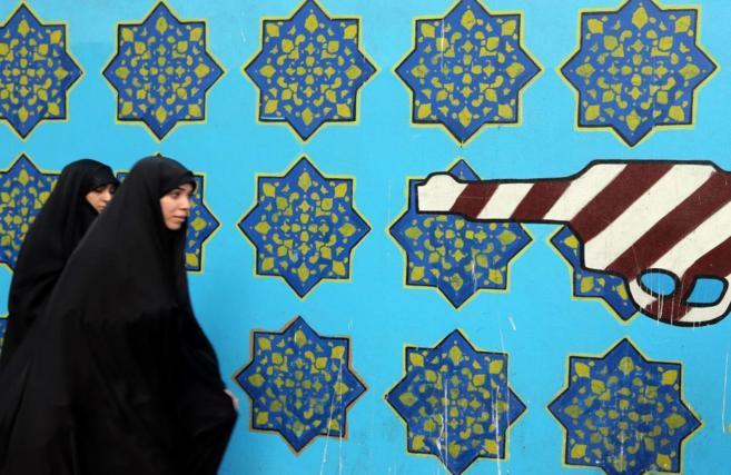 Mujeres iraníes pasan junto al muro de la antigua embajada de EEUU en...