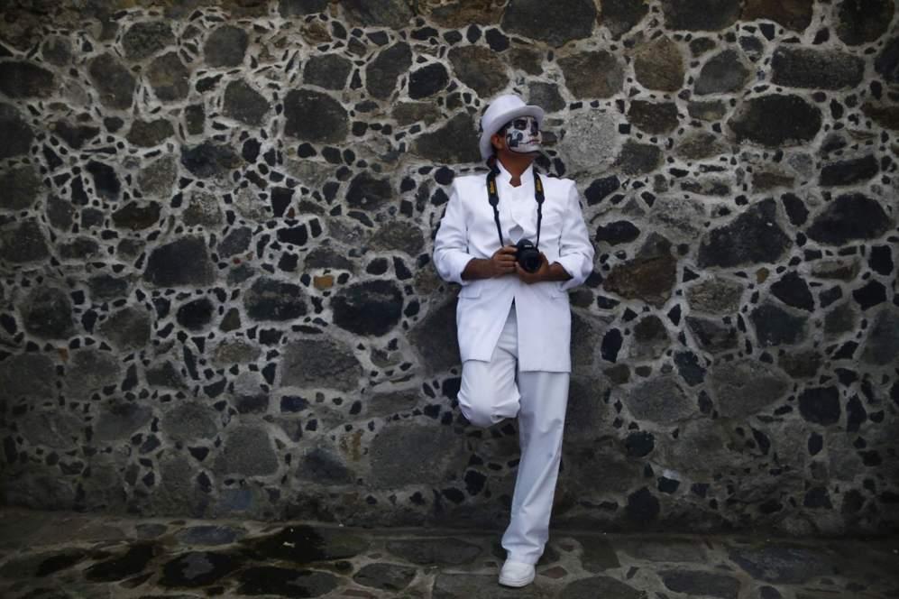 Un fotógrafo, con lacara pintada, posa para una foto en el cementerio...