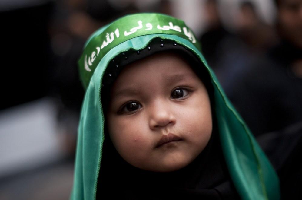 Un joven niño chiíta musulmán de Myanmar, se encuentra frente a una...