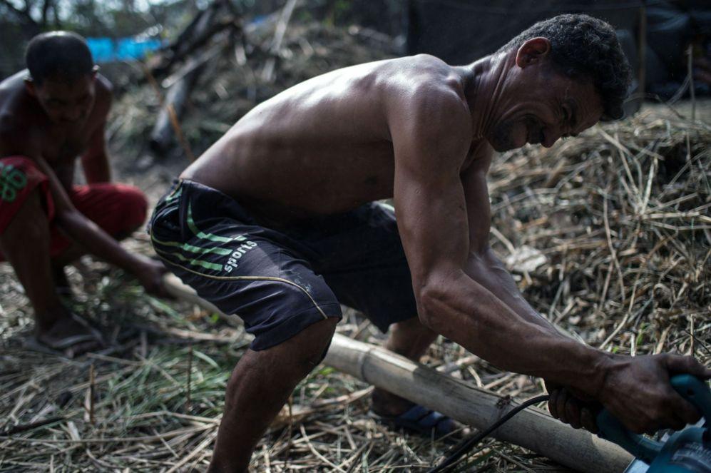 Wagner Leal (Dcha.) corta bambú para hacer una choza despues de que...
