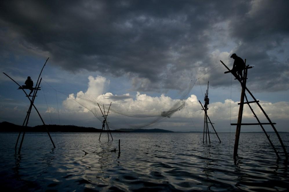 Esta foto muestra a los pescadores recogiendo una red vacía en...