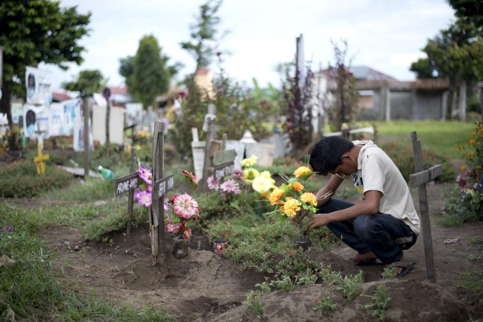 Esta foto muestra un pariente visitando las tumbas en frente de la...