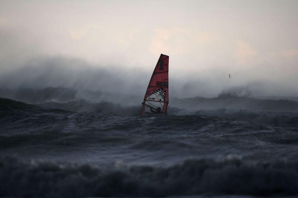 Un windsurfista cabalga las olas en la costa norte de Italia, en...