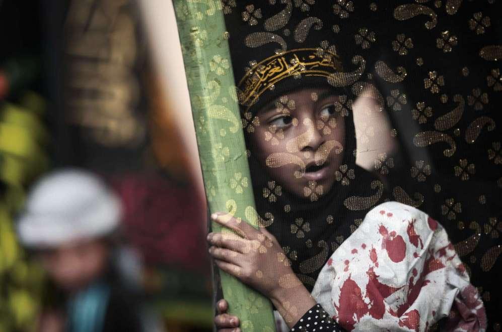 Una niña chií, de Bahrein, participa en una ceremonia para...