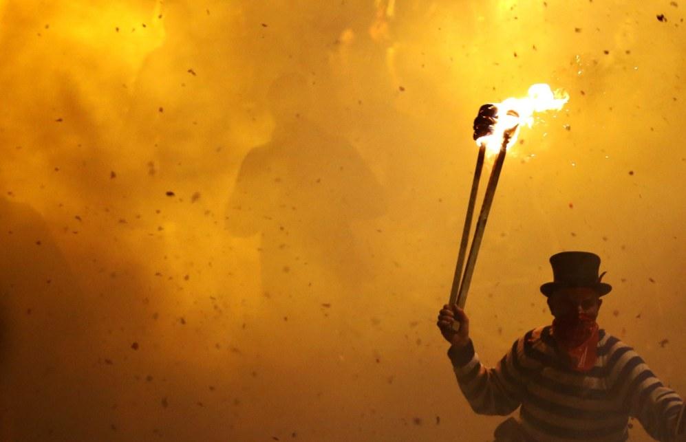 Participantes disfrazados sujetan antorchas encendidas, ya que...