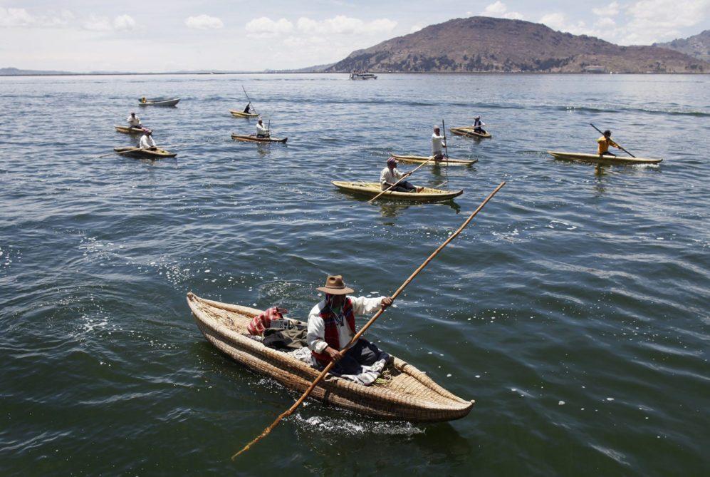 Los andinos reman en sus barcos de totora, mientras acompañan a los...