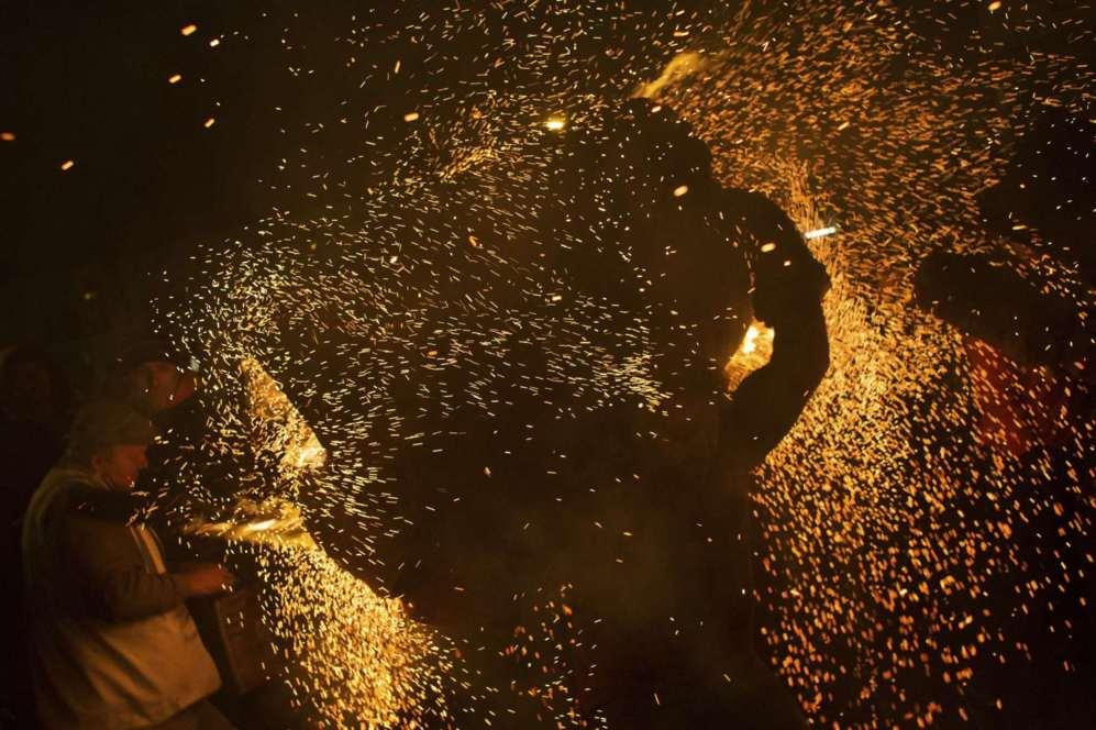 Un barril ardiendo empapado en alquitrán se pasea en llamas a través...