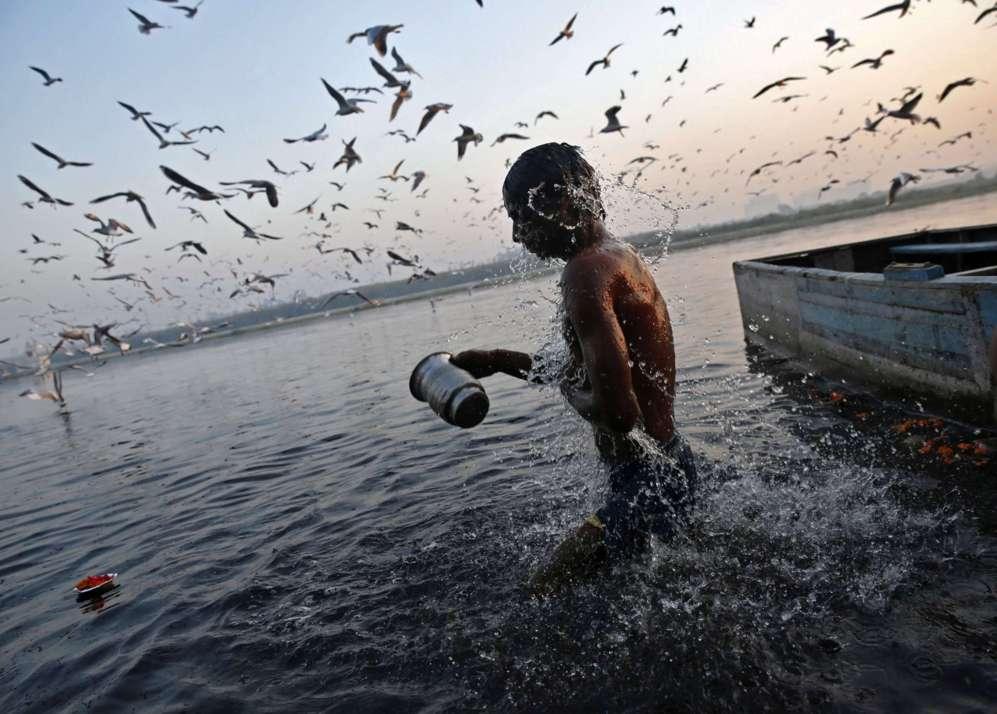 Un devoto hindú toma un baño en las aguas del río Yamuna.