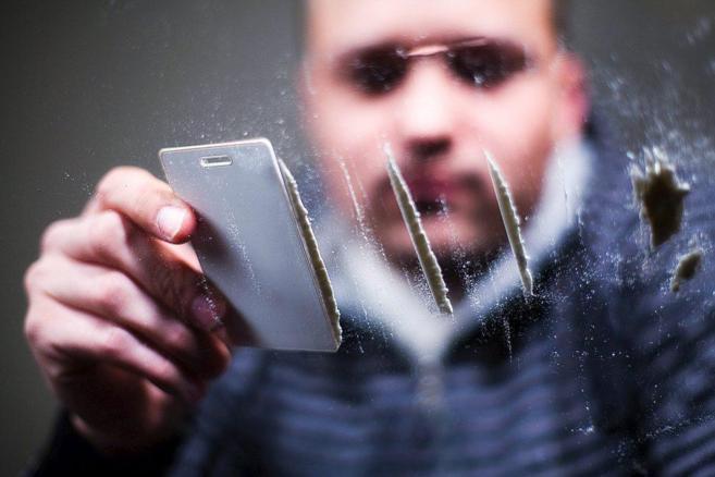 Un joven prepara varias dosis de cocaína.