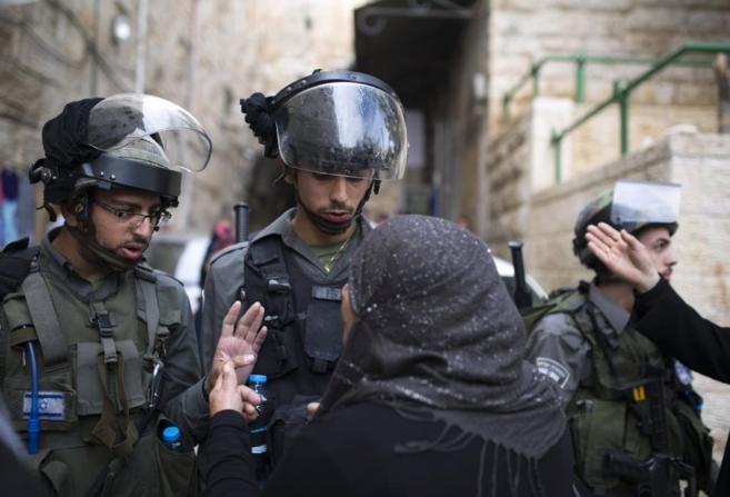 Una mujer palestina discute con dos agentes israelíes en la entrada...