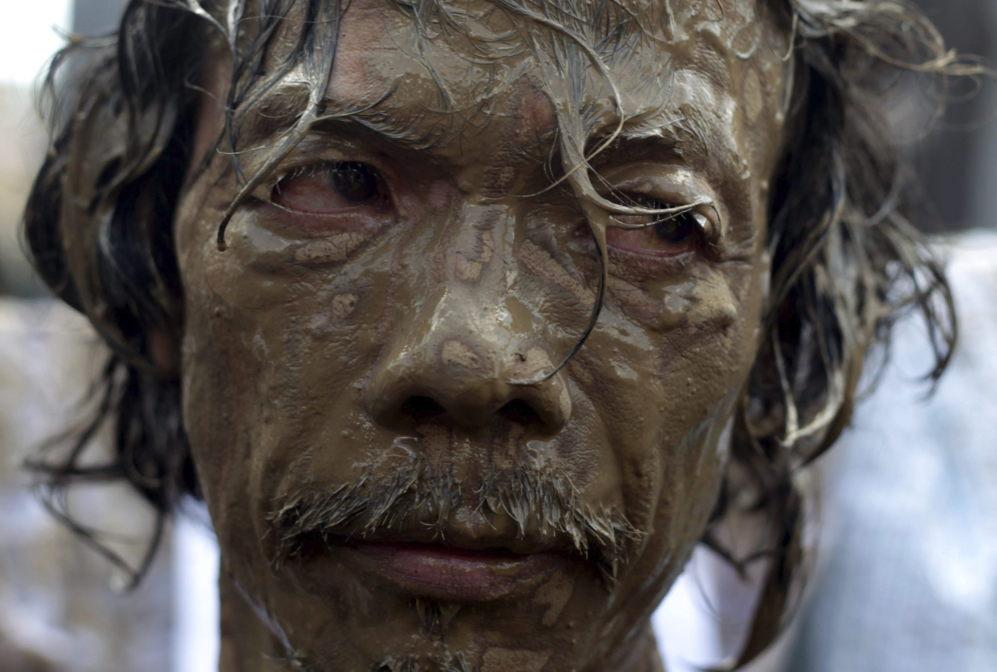 Un hombre con barro en la cara participa en una manifestación contra...