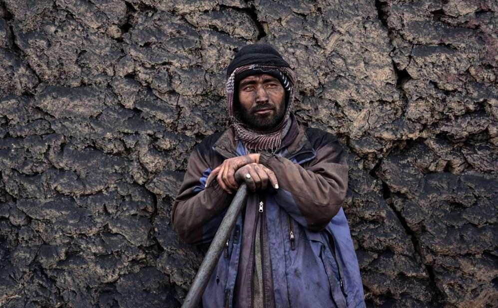 Un trabajador afgano se apoya en su pala mientras espera para cargar...