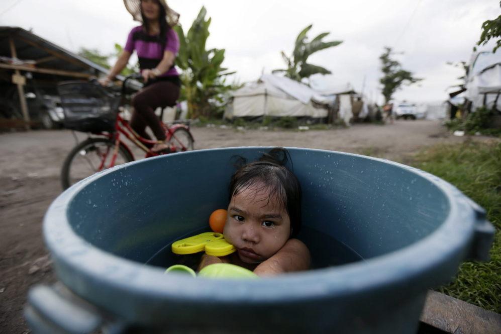 La joven Kyra Marie, de 3 años, se toma un baño en un campo de...