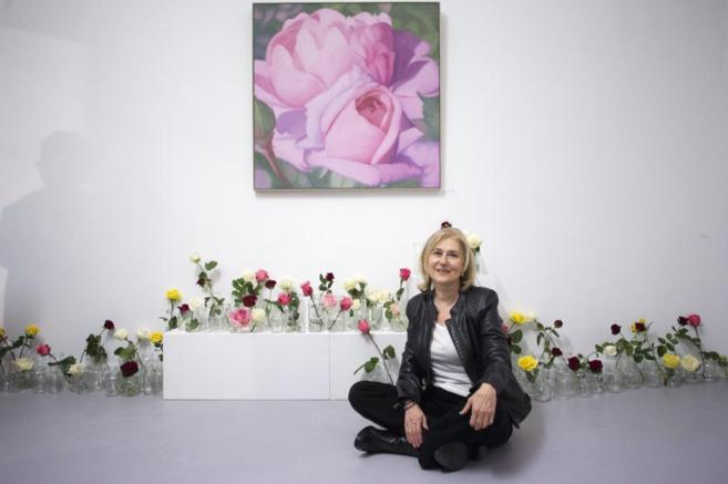 La pintora Maria Luisa M. Salmean posa junto a sus obras durante la...