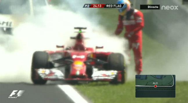 Alonso intenta apagar el fuego de su Ferrari.
