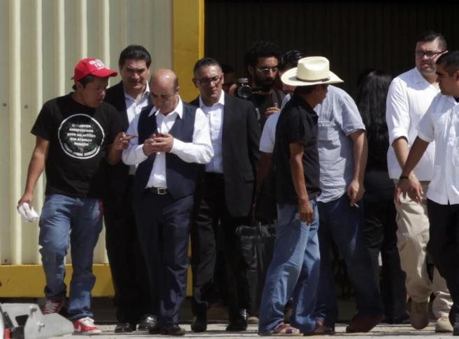 El procurador general Jesús Murillo (3 izda) sale del hangar tras...