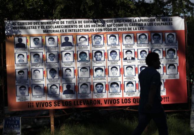 Un hombre pasa por delante de un cartel con los rostros de los...