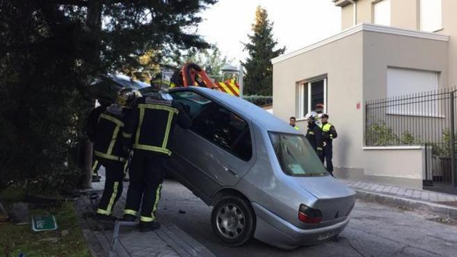 Los bomberos tratan de bajar el coche del tensor.