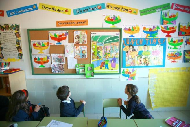 Tres niños miran al mural del aula en una clase de inglés.
