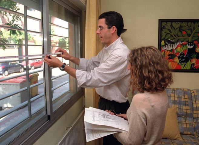 Un técnico es fotografiado durante la tasación de una vivienda, en...