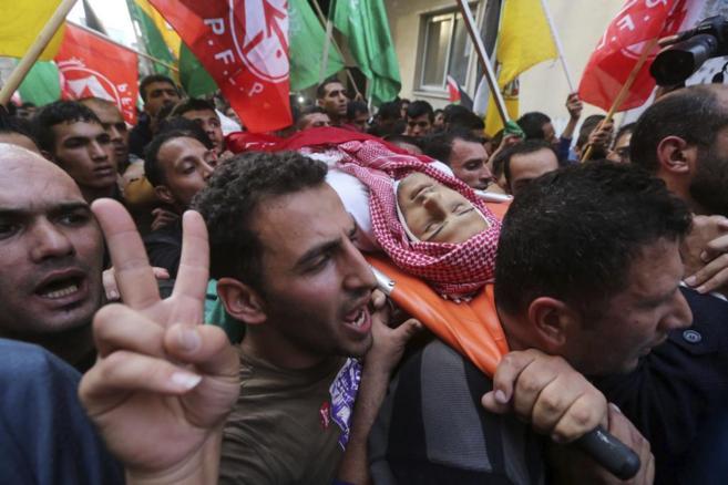 Palestinos portan el cadáver del joven fallecido en los recientes...